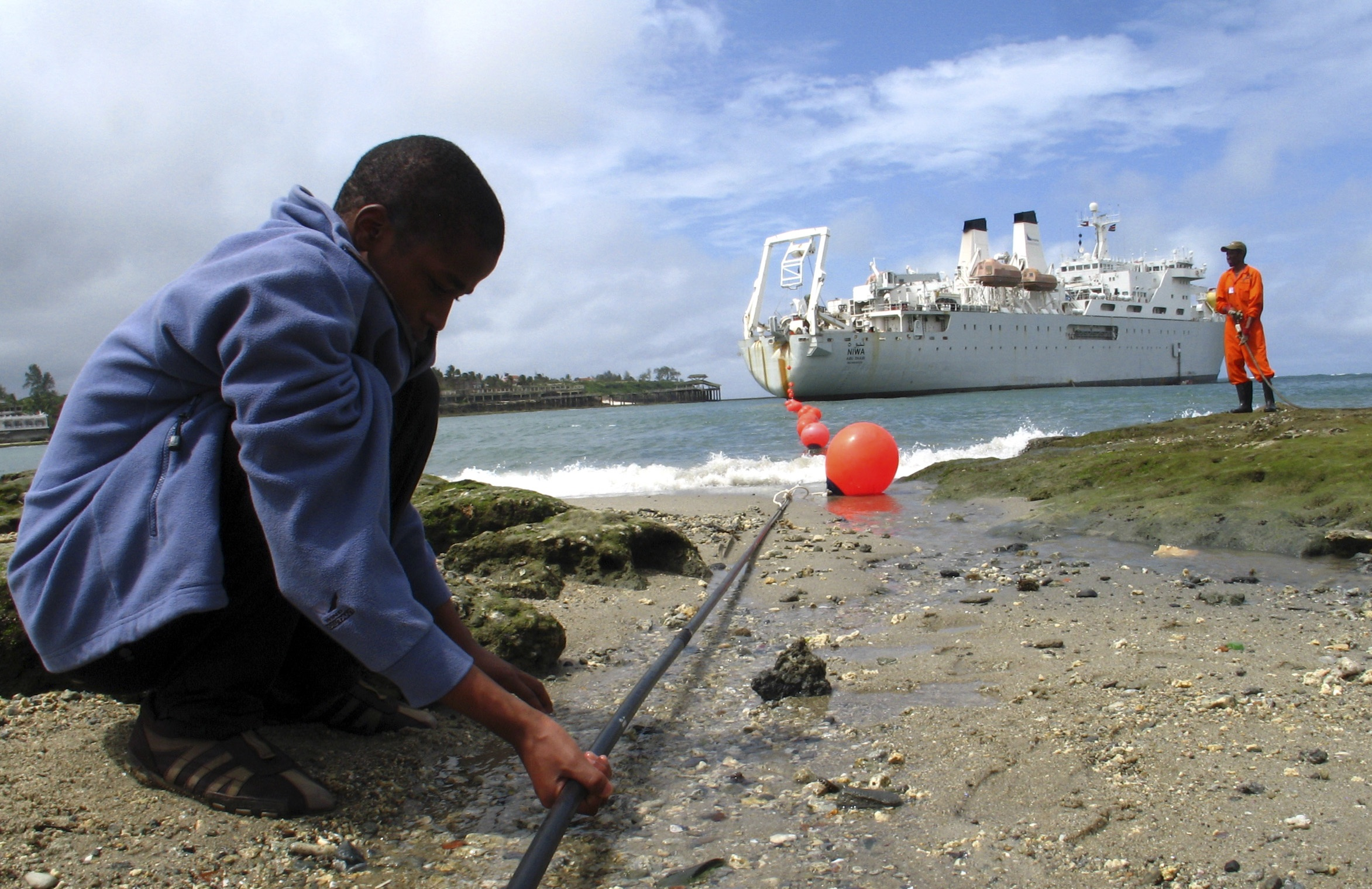 Kenyan boy looks at TEAMS fiber optic cable from the ship Niwa on the Fort Jesus shore-end in the coastal city of Mombasa