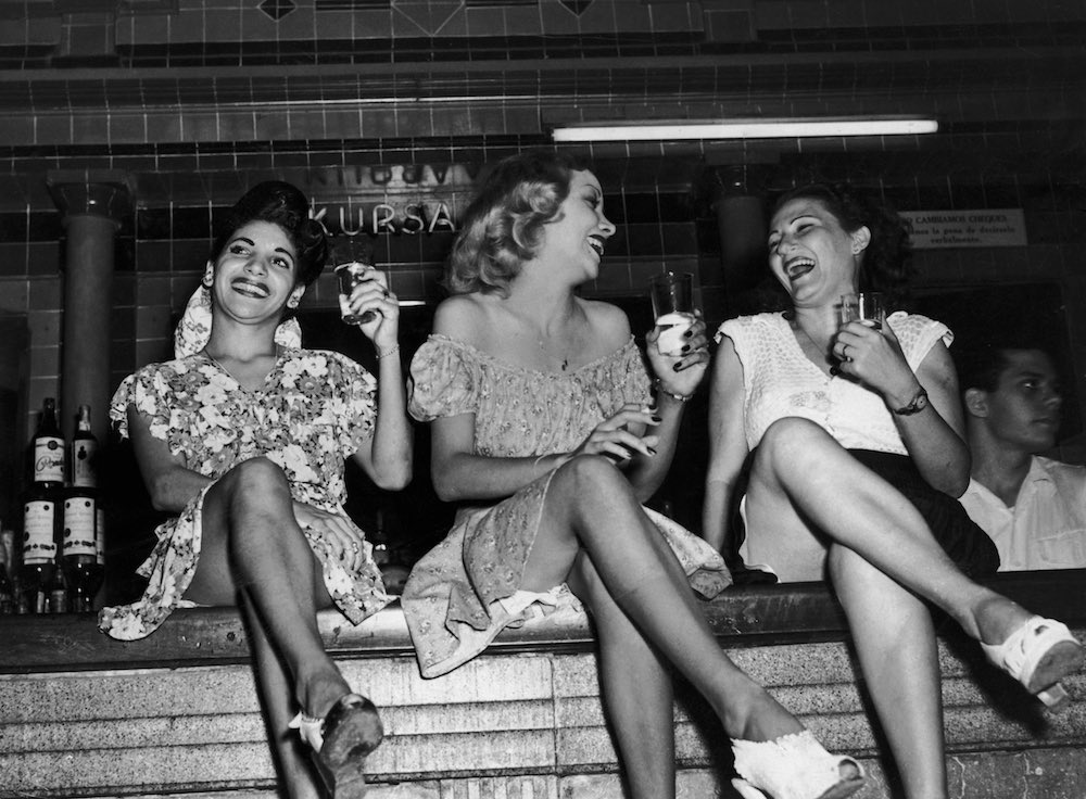 Three women perched on the bar at the Cabaret Kursal nightclub in Havana, Cuba, circa 1950. (Photo by Herbert C. Lanks/FPG/Hulton Archive/Getty Images)
