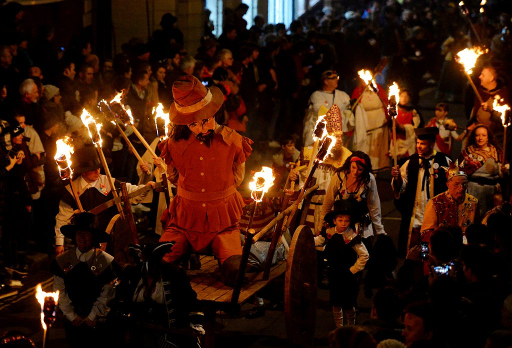 Bonfire societies parade through the streets with an effigy of Guy Fawkes during the Bonfire Night celebrations on November 5, 2013 in Lewes, Sussex in England. Bonfire Night is related to the ancient festival of Samhain, the Celtic New Year. Processions held across the South of England culminate in Lewes on November 5, commemorating the memory of the seventeen Protestant martyrs. Thousands of people attend the parade as Bonfire Societies parade through the narrow streets until the evening comes to an end with the burning of an effigy, or 'guy,' usually representing Guy Fawkes, who died in 1605 after an unsuccessful attempt to blow up The Houses of Parliament. AFP PHOTO / LEON NEAL (Photo credit should read LEON NEAL/AFP/Getty Images)